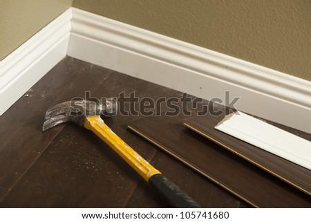 Hammer, Laminate Flooring and New Baseboard Molding Abstract. - stock photo