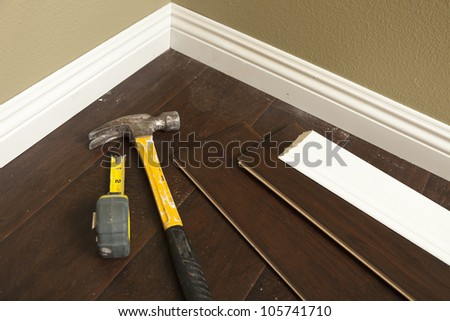 Hammer, Laminate Flooring and New Baseboard Molding Abstract. - stock photo