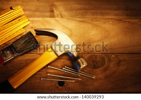Hammer, nails, ruler and brush on wood