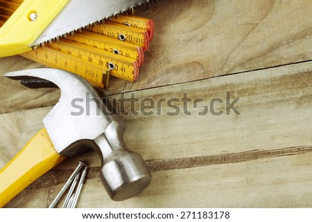 Hammer, nails, ruler and saw on wood - stock photo