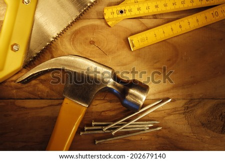 Hammer, nails, saw and folding ruler on wood  - stock photo