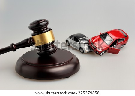 Hammer of judge with models of car accident on gray background - stock photo