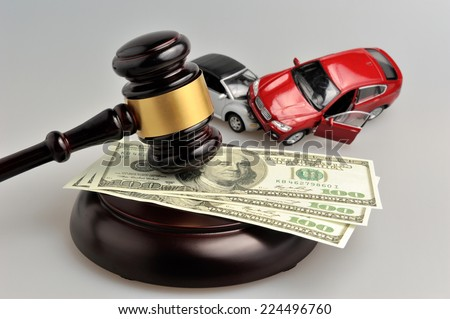 Hammer of judge with money and toy cars on gray background - stock photo