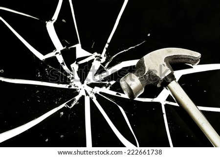 hammer on a black cracked glass - stock photo