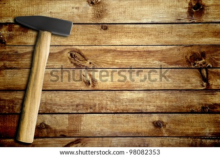 hammer on a wood board background