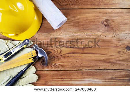hammer, protective gloves, folding ruler, model knife, blueprint and yellow safety helmet on wooden background
