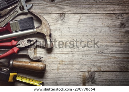 Hammer, screwdriver, wrench, tape measure, paint brush construction tools on wooden background with space for copy - stock photo