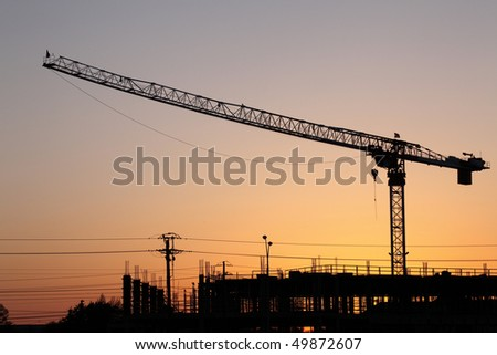 Hammerhead crane at a construction site silhouetted against the sky at sunset