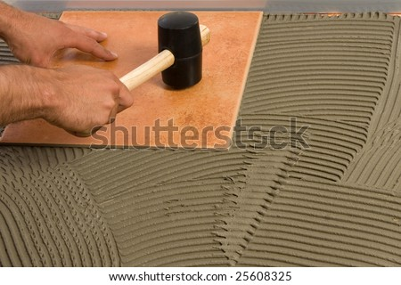 Hammering the tile in place - stock photo