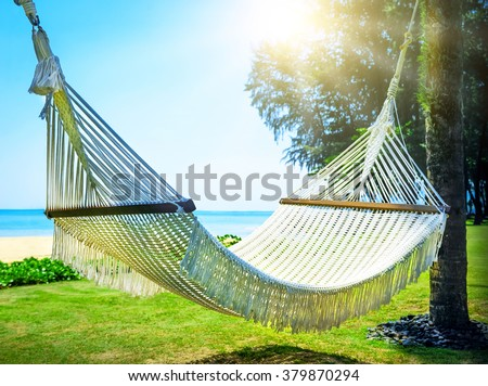 Hammock between two palm trees on the beach. Vacation concept - stock photo