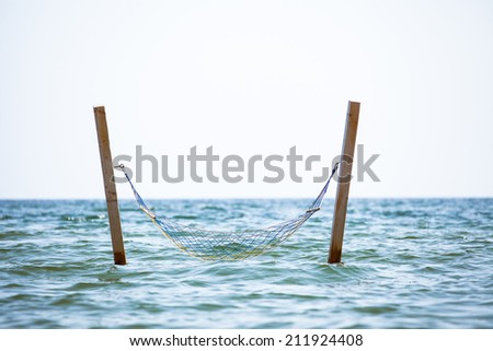 Hammock hanging over sea water - stock photo