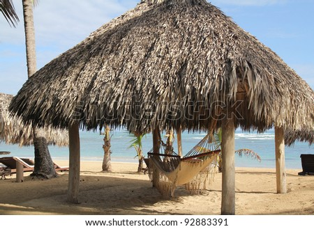 Hammock hangs in thatched hut next to Ocean - stock photo