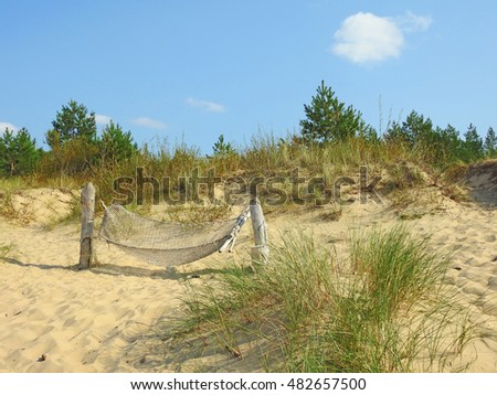 Hammock on a sand hill on a background of blue sea