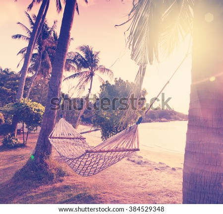 hammock on the shore of a tropical beach at sunset. Image with retro filter - stock photo