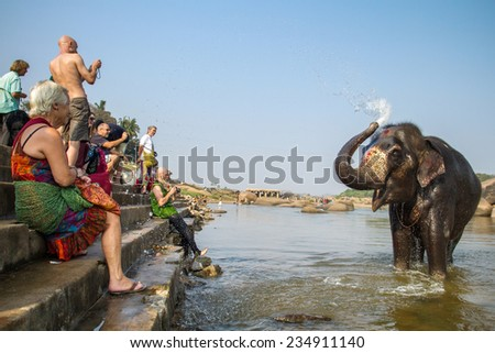 HAMPI, INDIA - FEBRUARY 1, 2013: Unidentified tourists watching Lakshmi, the temple elephant, taking a bath in the river on February 1, 2013 in Hampi, Karnataka, India - stock photo