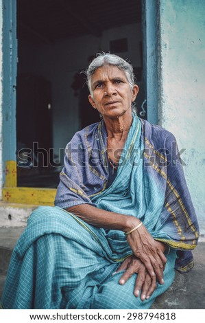 HAMPI, INDIA - 31 JANUARY 2015: Elderly Indian woman sits in sari in-front of home. Post-processed with grain, texture and colour effect. - stock photo