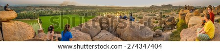 HAMPI, INDIA - 29 JANUARY 2015: Hilltop view of Hampi's boulder strewn landscape and rice paddies with tourists - stock photo