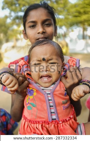 HAMPI, INDIA - 31 JANUARY 2015: Indian baby with bindi crying while being held by family member - stock photo