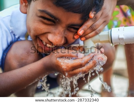 HAMPI, INDIA - 31 JANUARY 2015: Indian boy being teased while drinking water from a fauset - stock photo