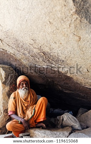 HAMPI, INDIA - 9 MARCH: Unidentified hindu ascetic, wandering monk sadhu in Hampi, India, March 9, 2012. During of celebration of Holi holiday 2012. Holi is also known as Festival of Colours. - stock photo