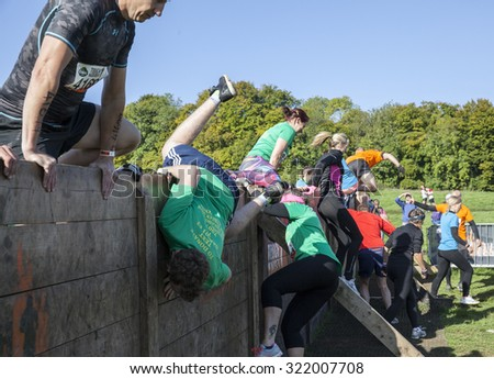 HAMPSHIRE, UK - SEPTEMBER 26, 2015: Tough Mudder is a team-oriented 18-20 km obstacle course testing strength and mental grit. It is not a timed race but a team challenge with world-class obstacles. - stock photo