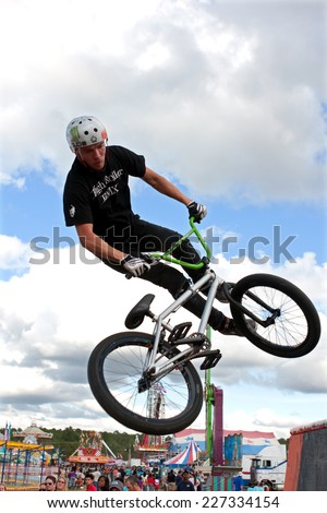 HAMPTON, GA - SEPTEMBER 27:  A young man with the High Roller BMX club spins his bike in midair while performing a BMX stunt at the Georgia State Fair on September 27, 2014 in Hampton, GA.