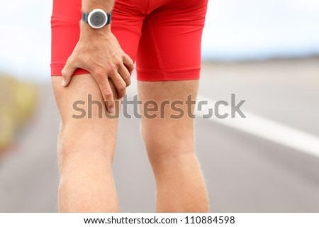 Hamstring sprain or cramps. Running sports injury with male triathlete runner. - stock photo