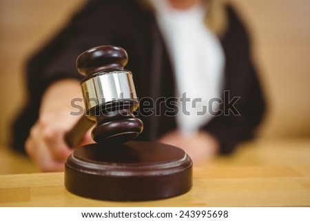 Hand about to bang gavel on sounding block in the court room - stock photo
