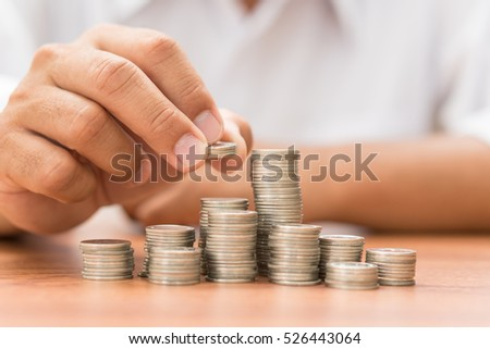 hand add coin to coin stack, saving money concept.