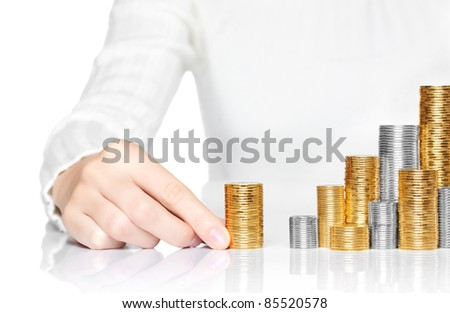 Hand adding a stack of coins to savings - stock photo