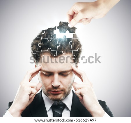 Hand adding last piece to pensive puzzle headed businessman on grey background. Business challenge and solution concept
