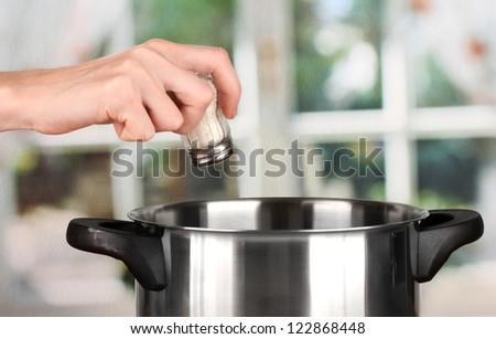 Hand adding salt using  salt shaker on bright background - stock photo
