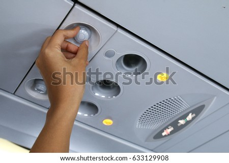 Hand adjusting air conditioning in aircraft cabin