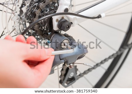 Hand adjusting bicycle's rear derailleur - stock photo