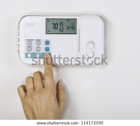 Hand adjusting inside home temperature to seventy degrees fahrenheit with White wall as background - stock photo