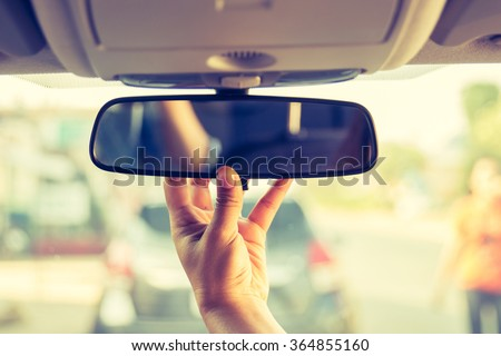 Hand adjusting rear view mirror. - stock photo