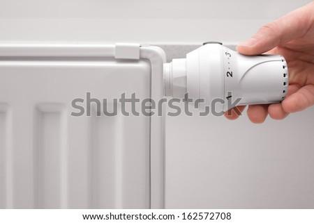 hand adjusting the temperature of heating radiator - stock photo