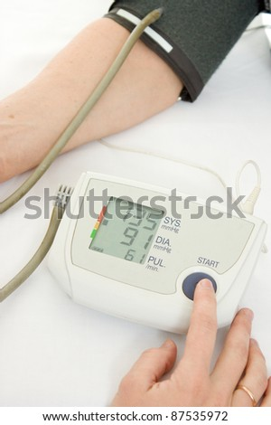 Hand an elderly woman with a sphygmomanometer on a white background. - stock photo