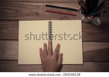 hand and a notebook on a wooden table. - stock photo