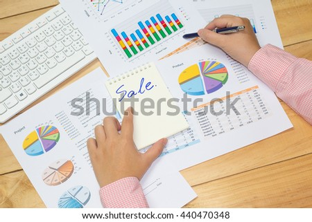 hand and arm business man point analysis financial paper charts and graphs on the wooden table background