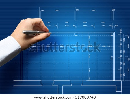 Hand and blueprint - engineer working on blue print concept