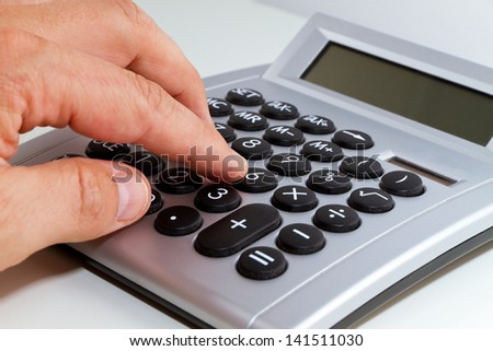 Hand and calculator - stock photo