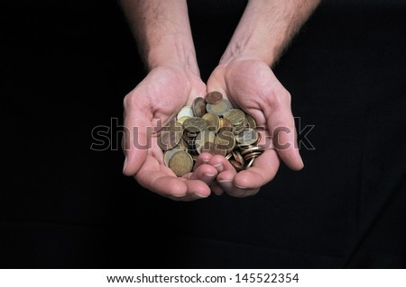 Hand and Coins Money over a Black Background