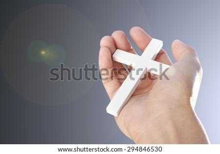 Hand and cross  - stock photo