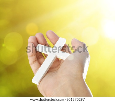 Hand and cross on bokeh background , concept design