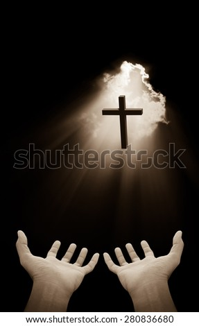 Hand and cross on light beams background - stock photo