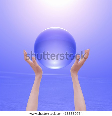 Hand and crystal ball with purple background  - stock photo