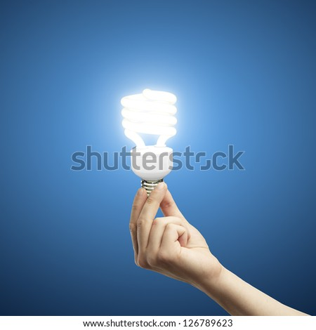 hand and energy saving lamp on blue background