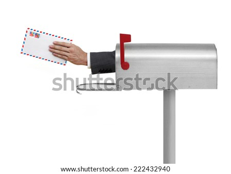 Hand and envelope with US stamp in a mailbox - stock photo