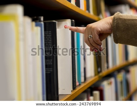 Hand and finger of woman selecting a book from book shelf - stock photo